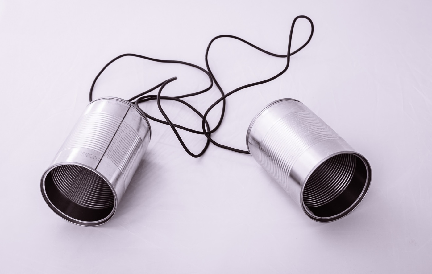 Picture of two cans linked by a thread