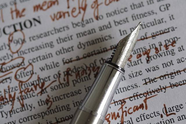 Picture of pen lying on a page of text riddled with corrections
